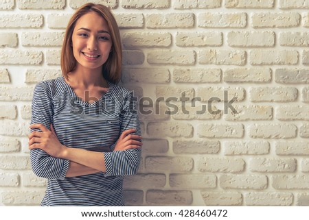 Beautiful Asian girl is looking at camera and smiling while standing with crossed arms against white brick wall - stock photo