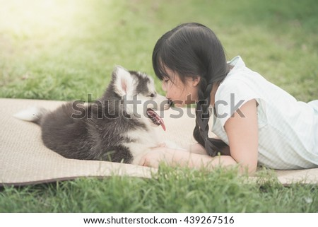 Beautiful asian girl playing with siberian husky puppy in the park,vintage filter - stock photo