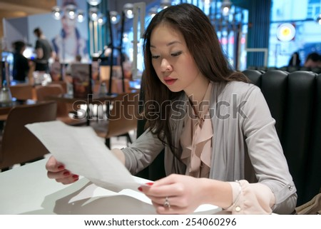 Beautiful Asian girl reading a letter - stock photo
