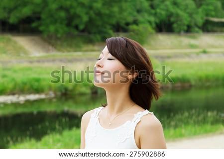 Beautiful Asian girl relaxing in green - stock photo