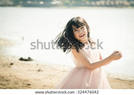 Beautiful asian girl smiling on the beach,Vintage filter - stock photo