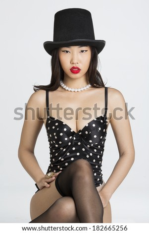 Beautiful Asian girl wearing Top Hat and lingerie against white background - stock photo