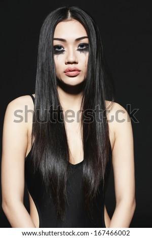 Beautiful Asian girl with black mascara under eyes - stock photo