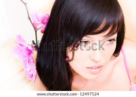 Beautiful asian girl with orchid. Low DOF, focus on eyes - stock photo
