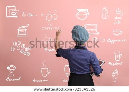 Beautiful Asian girl writing coffee menu on pink wall - stock photo