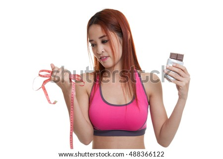 Beautiful Asian healthy girl with chocolate and measuring tape  isolated on white background.