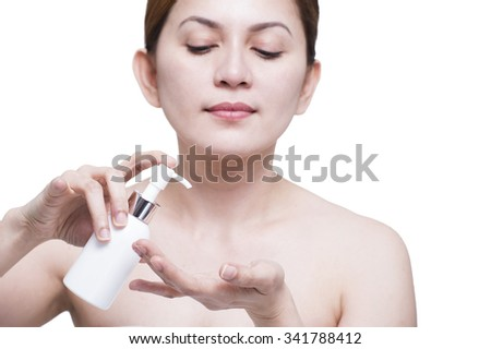 Beautiful asian lady model squeezing a bottle of moisturizer into her hand. Isolated in white background.
