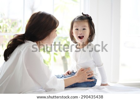 Asian mother and daughter kissing