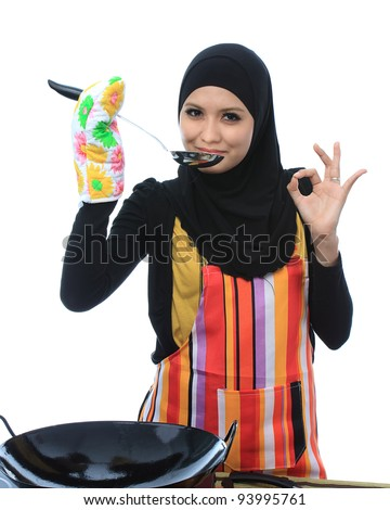 Beautiful asian muslim woman tasting and showed signs delicious while looking to the camera in the kitchen isolated white background - stock photo