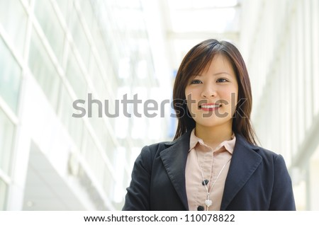Beautiful Asian officer walking by modern building - stock photo