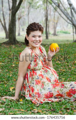 Beautiful asian pregnant woman sit on lawn in public park hold one orange fruit in hand - photo taken 2 days before baby birth - stock photo