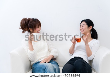 beautiful asian sisters talking each other - stock photo