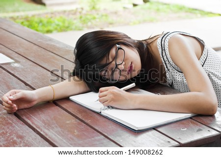 Beautiful Asian student woman tired and sleep. - stock photo
