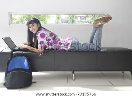Beautiful Asian student working with laptop and books