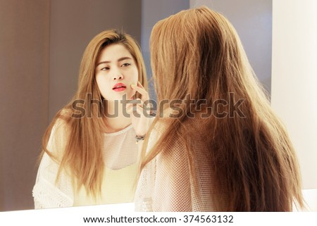 Beautiful Asian teenage girl touching her face before the mirror in bathroom - stock photo