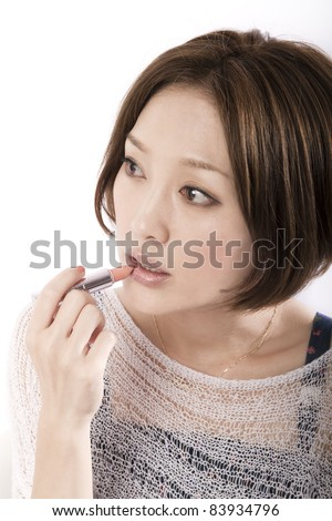 Beautiful asian woman applying lipstick