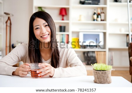 beautiful asian woman drinking a glass of tea - stock photo