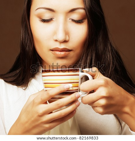 Beautiful asian woman drinking coffee or tea - stock photo