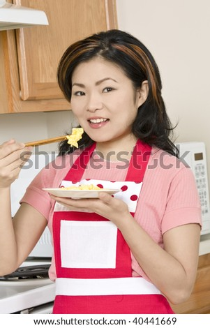 Beautiful Asian woman eating eggs with chop sticks in the kitchen