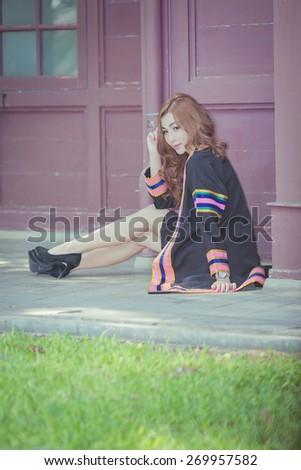 Beautiful asian woman graduating sitdown in the garden