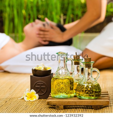 Beautiful Asian woman having a wellness Head massage in a tropical setting and feeling visibly good about it - Essential oils are in the foreground - stock photo