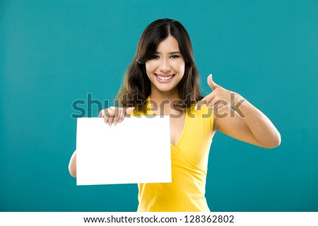 Beautiful asian woman holding and pointing to a blue billboard, over a blue background - stock photo
