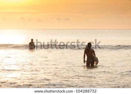 Beautiful asian woman in bikini in the surf with board - stock photo