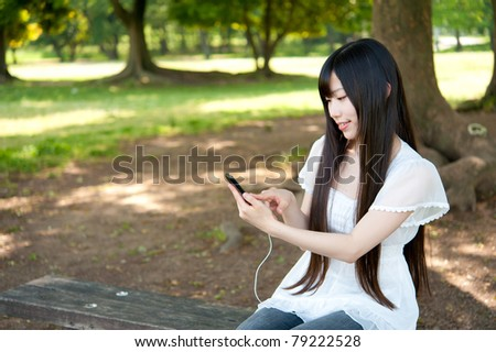 beautiful asian woman listening music in the park - stock photo