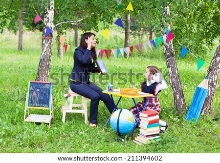 Beautiful asian woman mother teacher talking reading book to schoolgirl outdoors, back to school - stock photo