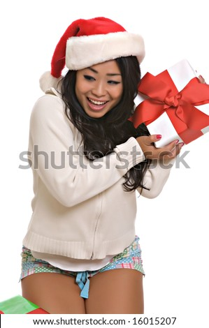 Beautiful Asian woman opening Christmas presents