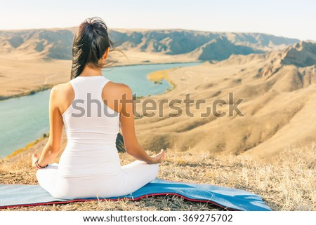 Beautiful asian woman relaxing and meditating outdoor at mountain. China. Sits at peak of mountain in lotus position, feel harmony of your body and nature. Healthy lifestyles concept of body and soul - stock photo