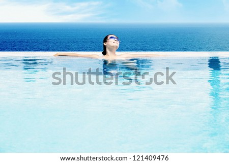Beautiful Asian woman relaxing in swimming pool - stock photo
