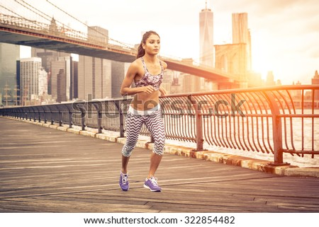 beautiful asian woman running in New york at sunset time. Brooklyn bridge and Manhattan skyline in the background - stock photo