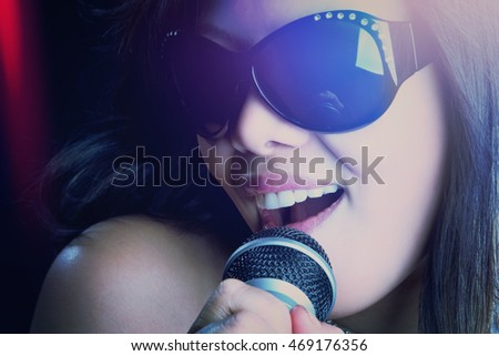 Beautiful asian woman singing wearing glasses
