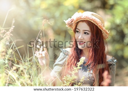 Beautiful Asian Woman Smiling And Touch Grass In Park .Playful and Beautiful mixed race girl on warm sunny day.