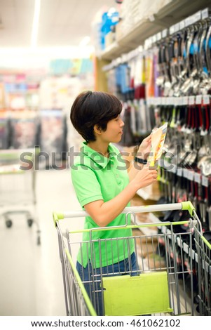beautiful asian woman so happy shopping kitchenware in a supermarket