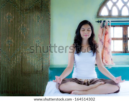 Beautiful asian woman training yoga and meditating, sitting in a bedroom with  arabian architecture background - stock photo