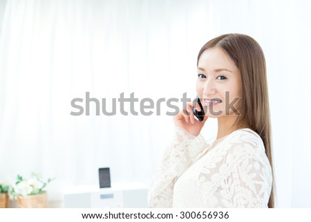 Beautiful asian woman using a cellular in the room - stock photo