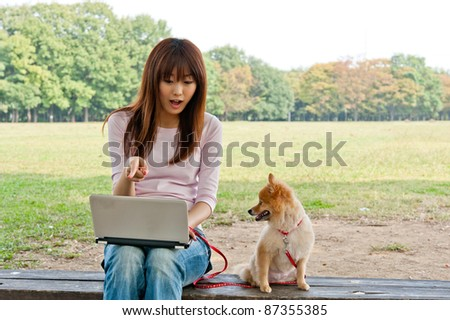 beautiful asian woman using laptop with dog in the park