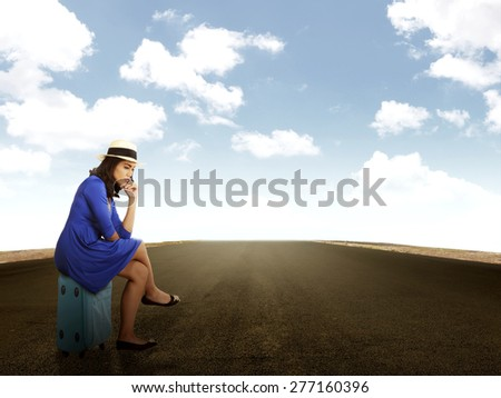 Beautiful asian woman waiting alone on the road. Travel alone concept - stock photo