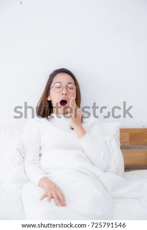 Beautiful asian woman waking up and yawn in bed in the bedroom, healthcare concept.