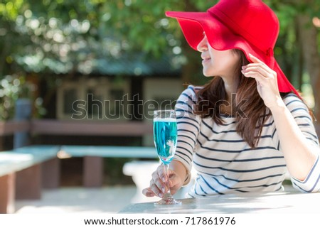 Beautiful asian woman wearing red velvet hat, holding a glass of blue cocktail, and looking at the beautiful scenery outside. Holiday and relax concept.