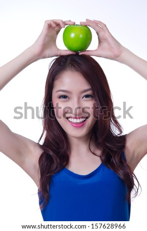 Beautiful asian woman with a green apple on head