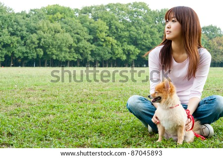 beautiful asian woman with dog sitting in the park