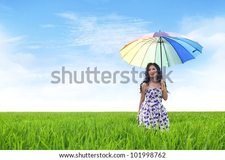 Beautiful Asian woman with umbrella on rice field