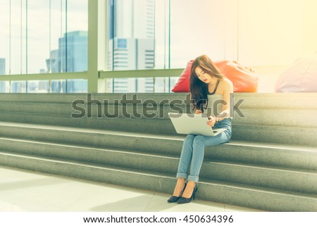 Beautiful Asian women using a laptop computer sitting on the stairs with concentrate.Vintage tone with city view background.