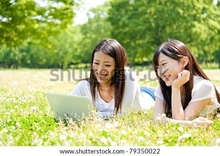 beautiful asian women using laptop in the park - stock photo