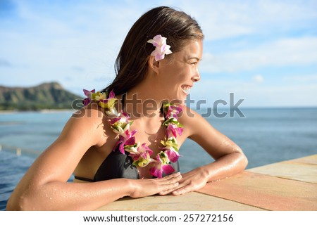 Beautiful Asian young adult relaxing in the sun with lei and Diamond Head on Waikiki, Oahu, Honolulu, Hawaii. USA vacation destination. - stock photo