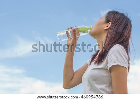 Beautiful asian young girl drinking water outdoor