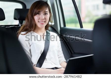 Beautiful asian young woman using laptop in car  - stock photo